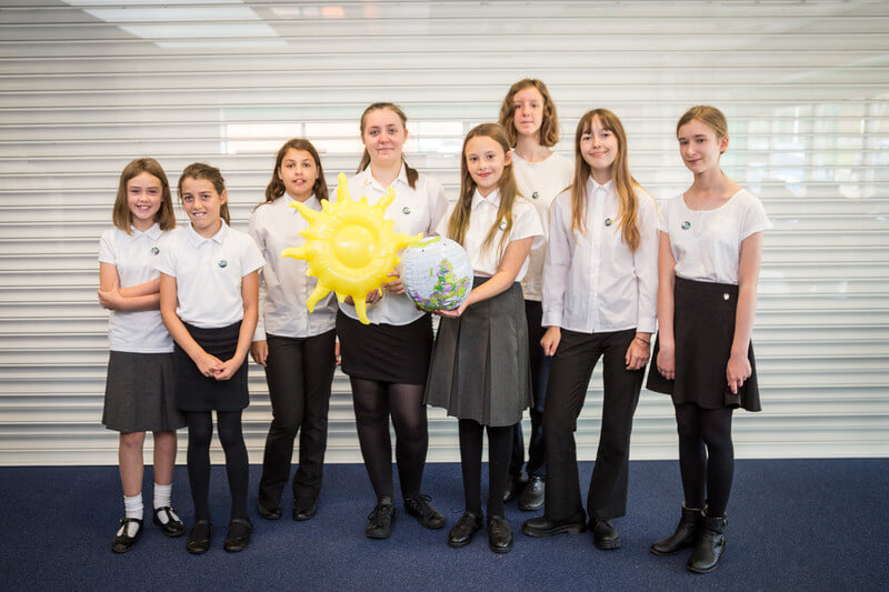 ECO2 Educational resources group of pupils with sunflower highlighting the role plants play in the environment